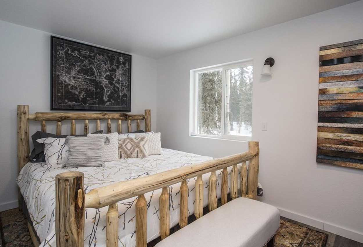 Queen bed with white sheets next to window and a painting on the wall inside RodFather Lodge