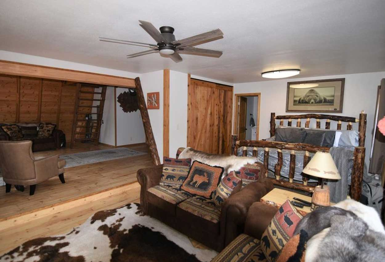 Master Bedroom inside RodFather Lodge with barn door, ceiling fan and furniture