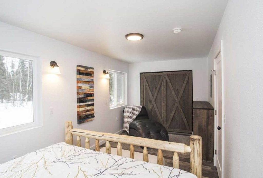 Bedroom with comfy furniture and barn door with two large windows inside RodFather Lodge