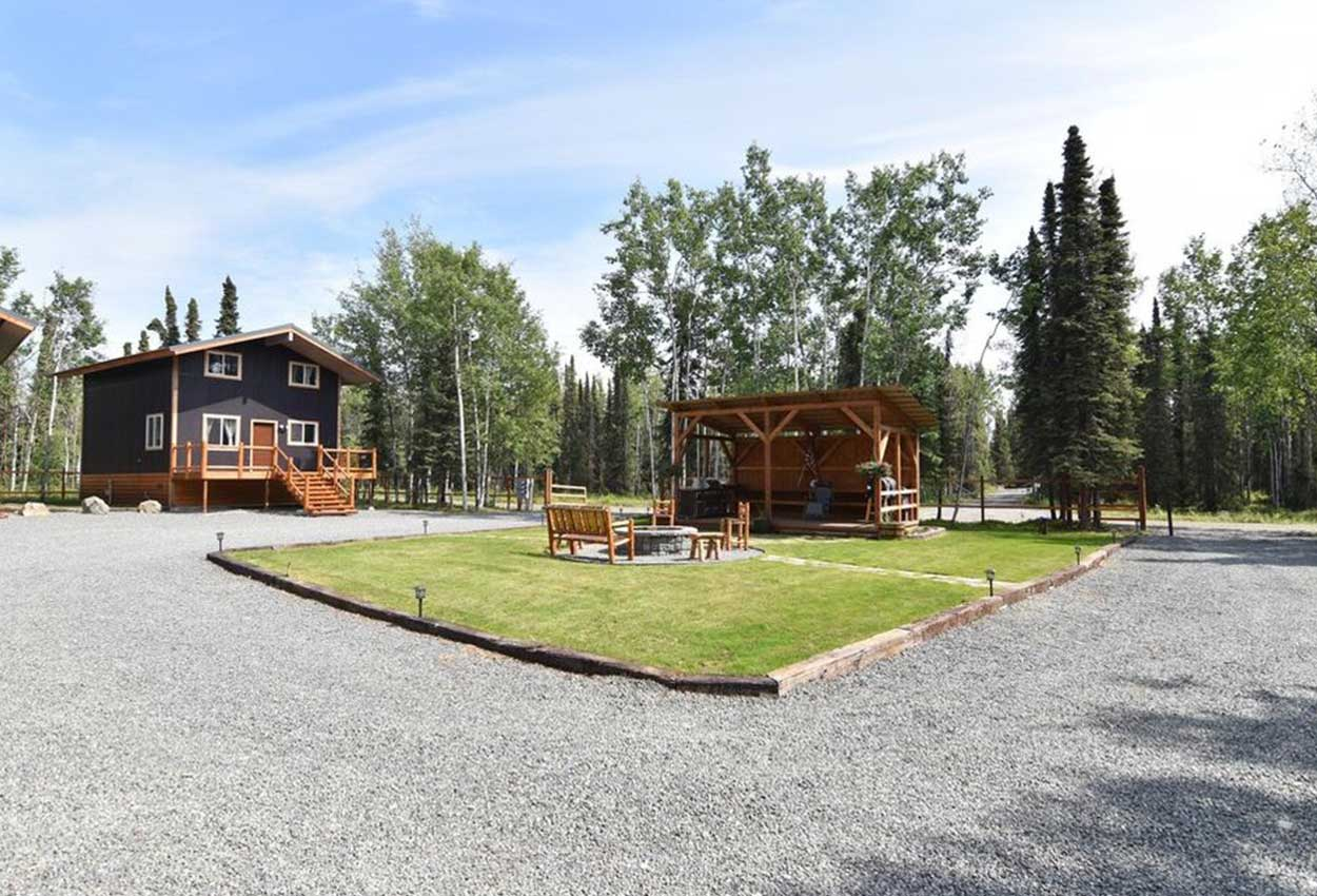 Outside Fire pit area with grassy playground RodFather Lodge